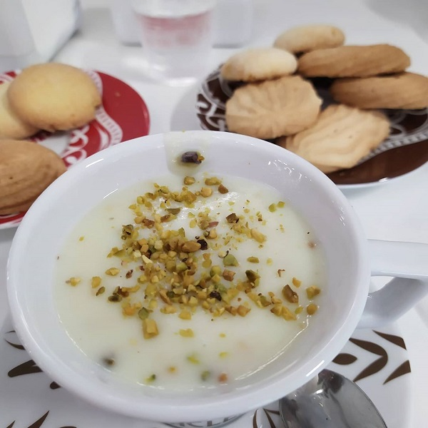 A cup of pistachio flavoured hot chocolate with biscuits