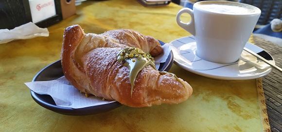 A pistachio cream croissant with cappuccino