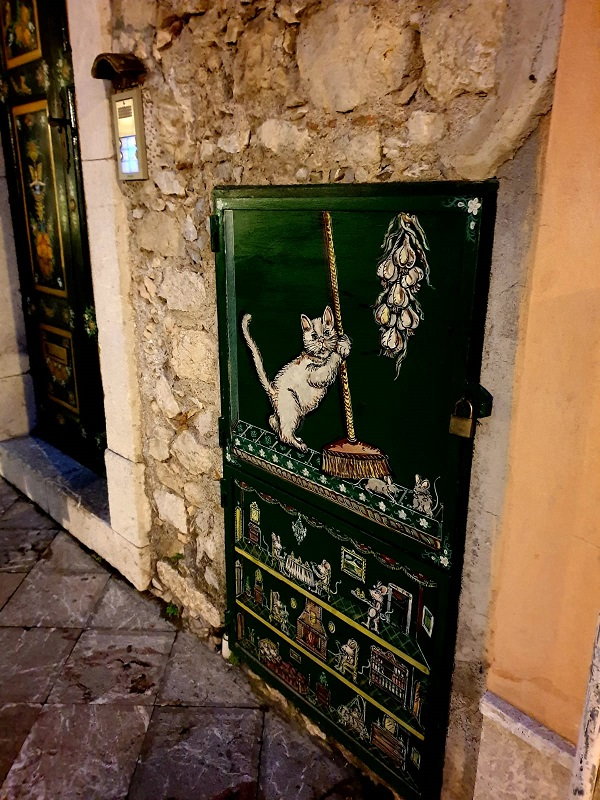 A street with art decorative panels showing a cat